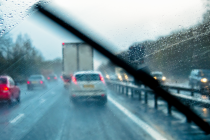 Vehicles driving along dual carriageway in the rain (wipers on)